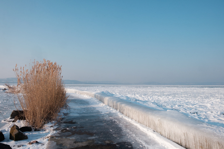 Icicles and ice at frozen lake Balaton, hills in background.