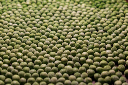 green deep frozen garden peas on brown wooden desk - above, close up