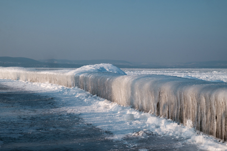 icicles at frozen lake Balaton, mountains in background. Imagens