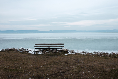 lonely bench at the frozen lake - summer is far