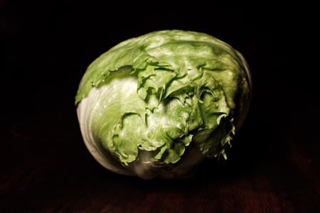 green iceberg lettuce head on dark brown wooden desk in spotlight - close up