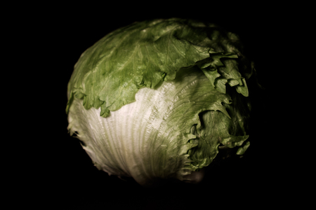 raw and fresh iceberg lettuce head on dark brown wooden desk in spotlight - close up Imagens