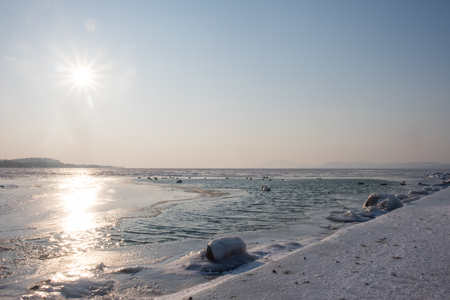 blue freezes lake in the afternoon, hills in background, Balaton, Hungary