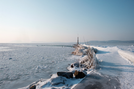 frozen lake, light tower and port covered by ice, afternoon, Balaton, Hungary, shape of hills in background
