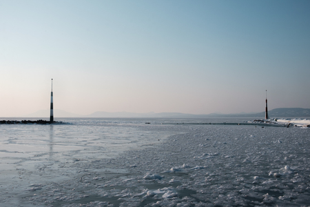 frozen lake with light towers, afternoon, Balaton, Hungary, shape of hills in background