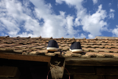 black shoes walking on rooftop - ceramic tiles, blue sky symbol of unrealistic ideas, be zonked out Stock Photo