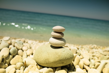 stack of pebbles balance harmony zen - ocean or sea shore, refreshing blue waves summer, beach, vintage style Imagens - 99270143