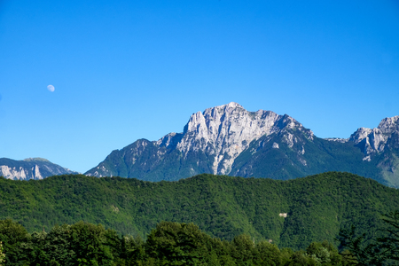 High craggy mountains with rising moon and blue sky in Bosnia and Herzegovina Imagens