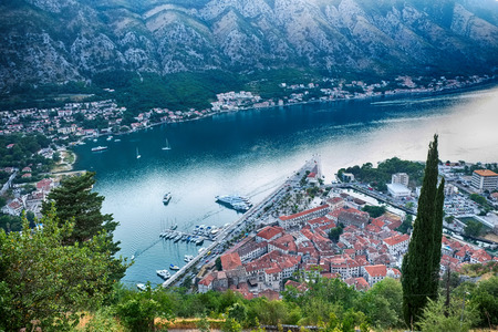 old mediterranean town and bay of Kotor city late afternoon - sail boats, ships on water, tones