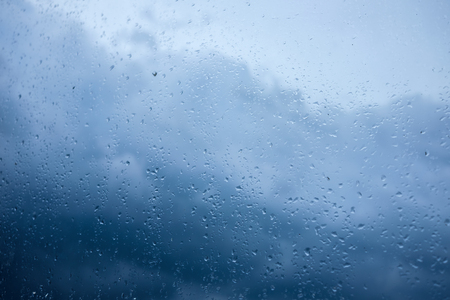 rain drops on glass blue clouds rainy mood, down with cold,