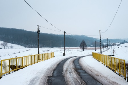 snowy winter landscape, asphalt road across yellow bridge leads in to the hills, pylons and wires follow the path Imagens