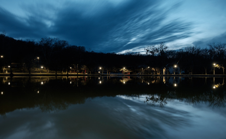mirrored clouds and lights on lake water in the afternoon, trees with bare branches and cold