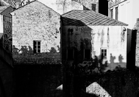 people silhouette on medieval stone house wall, Mostar, Bosnia and Herzegovina, black and white, concept Imagens - 99337601