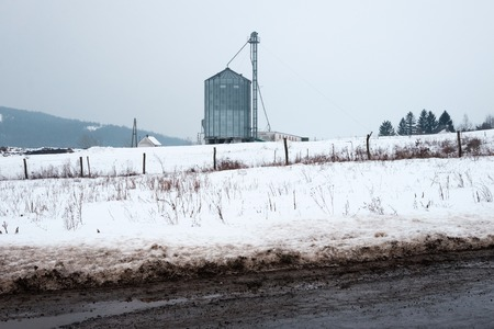 lonely granary stands on the ground, dirty road and fence in foreground, landscape covered by snow
