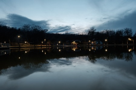 calm water reflecting clouds and light spots at a lake in the afternoon, trees with bare branches and cold
