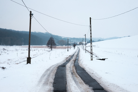 snowy winter landscape, asphalt road leads in to the hills, pylons and wires Imagens