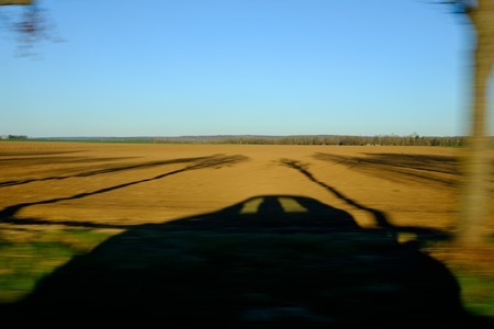 projected car shadow on brownish field in the spring - blurred image Imagens