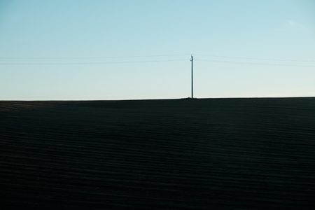 pylon standing on plow land hill - dark shadows Imagens