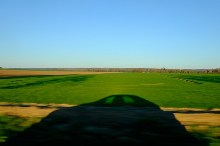 projected car shadow on green field - blurred image