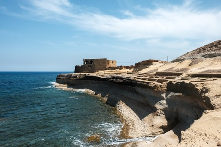 salt pans and abandoned building at Gozo islands, Malta Imagens - 101601571