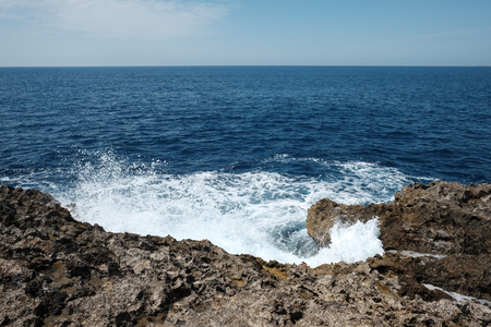 sea waves crashing on sharp cliffs, Gozo island, Malta