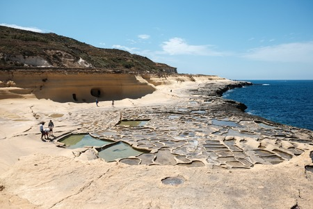 yellow sandstone rocks and caves and salt pans at the sea, near to Marsalforn, Gozo island, Malta