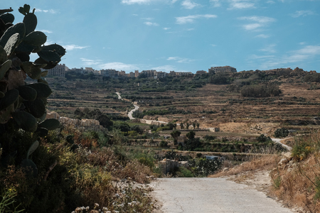 Gozo island landscape with hills and town and sinuous road Imagens - 102017781