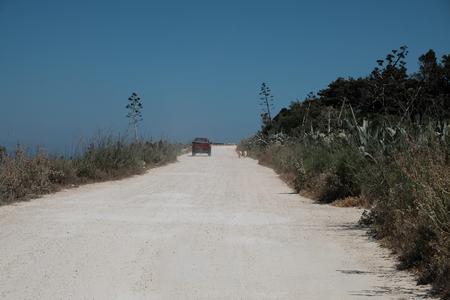 red pickup on dirty road and barking dog - mediterranean scene - Gozo island, Malta