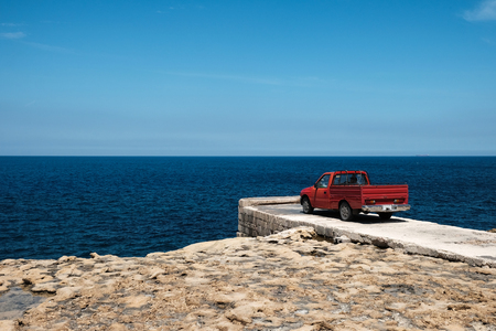red pickup car staring at the blue sea