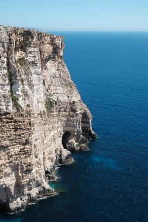 high Ta Cenc Cliff and the blue sea at Sannat, Gozo island, Malta Imagens - 105402814