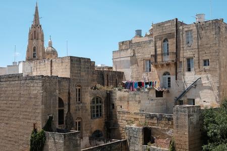morning on rooftop - Maltese houses, church tower at Ghajnsielem, Gozo island, Malta Imagens