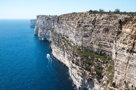 a boat swimming at Ta Cenc Cliff at Sannat, Gozo island, Malta - walls of the giants