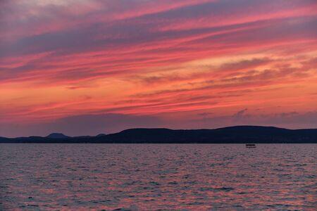 lake Balaton sunset pink and purple clouds, dark tones