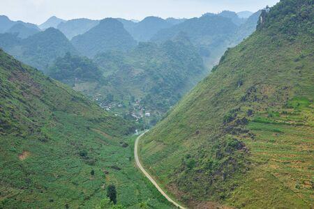 thin road between steep mountain slopes Ha Giang province, north Vietnam