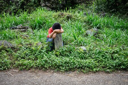 tired young vietnamese boy is relaxing at the road edge in Ha Giang province, north Vietnam Imagens