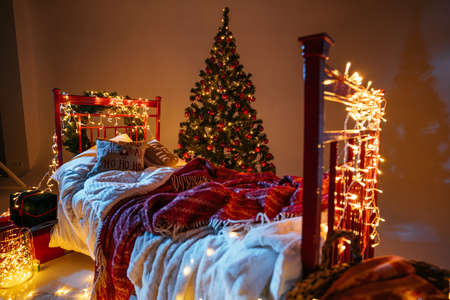 New Year 2021 interior with candles, bulbs and bokeh. Room decorated to christmas celebration. Christmas tree with presents Banque d'images