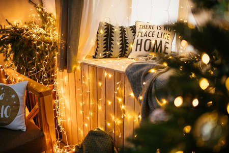 New Year 2021 interior with candles, bulbs and bokeh. Room decorated to christmas celebration. Christmas tree with presents