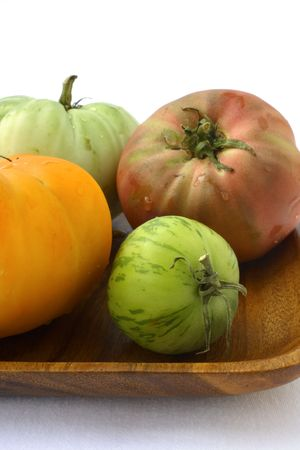 Fresh heirloom Tomatoes on wooden plate, white background Stock fotó