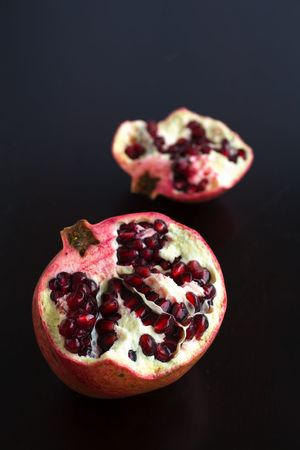 pomegranates cut open with pomegrante seeds showing