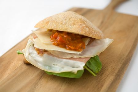 Ham and Cheese Sandwich with prosciuto ham, parmesan cheese, roasted red peppers, arugula, on fresh chabitta bread