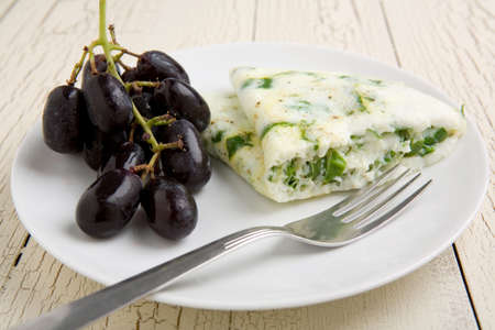 Egg white and spinach omelet with fruit on a white plate Banco de Imagens
