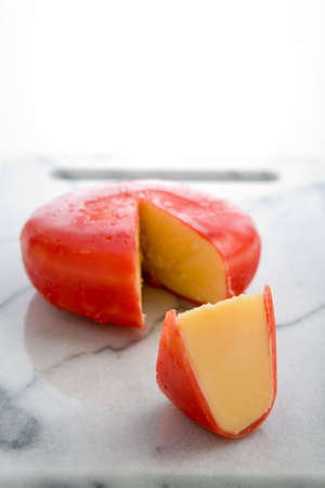 A wheel of gouda cheese covered with red wax, with a wedge cut out form the wheel Stock Photo
