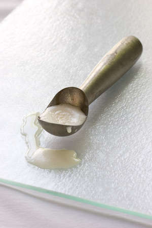 pooled: ice cream scoop with melted vannila ice cream in the scoop
