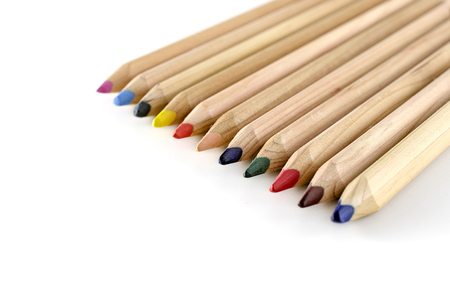 Wooden colorful pencils lying in a row