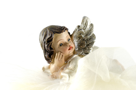 Christmas angel on a white cloth and feathers