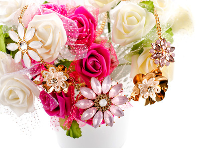 A variety of flowers in a vase with a jewel on top Stock Photo