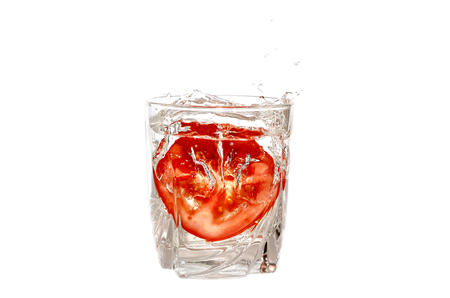 Tomato fallen into a glass of water