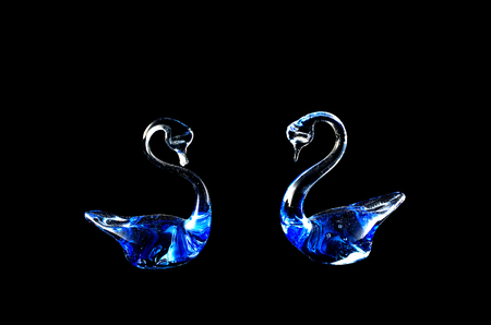 a pair of glass beautiful swans on a black background