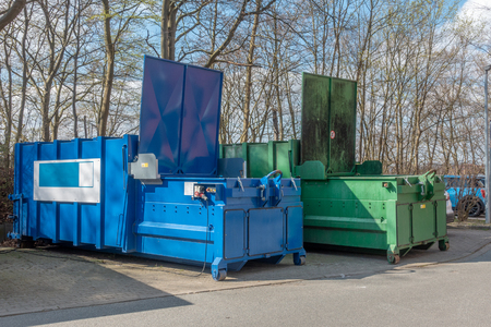 two large garbage compactors standing on a hospital site Imagens