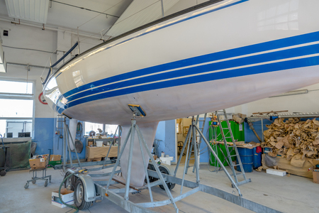 a sailing ship stands in a paint shop to be repainted